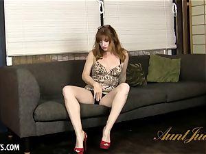 bodacious mature Amber Dawn seductively massages her muff